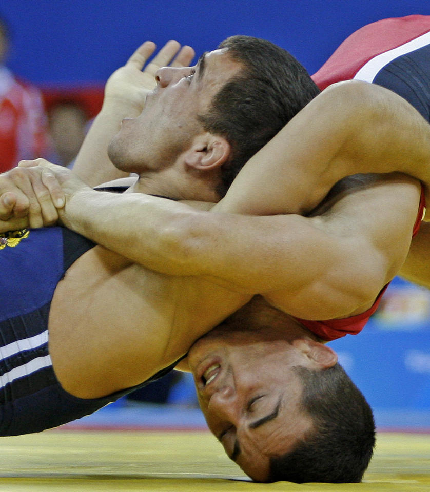 Russia's Nazyr Mankiev wearing blue wrestles with Azerbaijan's Rovshan Bayramov during their 55 kilogram greco-roman gold medal wrestling match at the Beijing 2008 Olympics in Beijing Tuesday, Aug. 12, 2008. (AP Photo/Ed Wray)