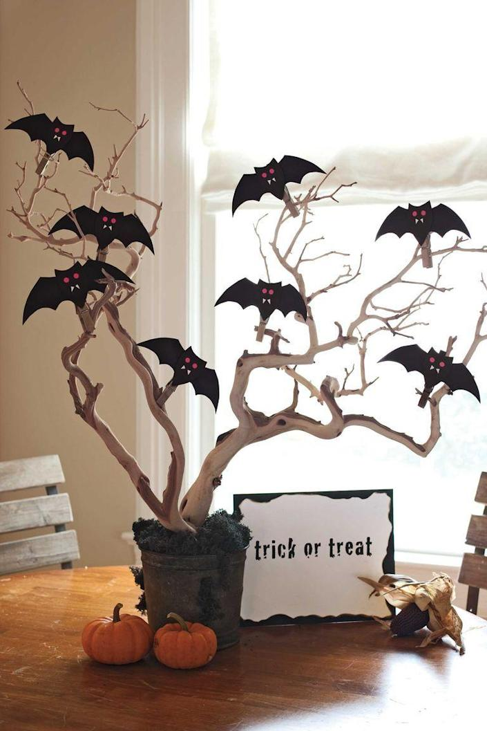 """<p>Perch beady-eyed paper bats on boughs for a spooktacular tabletop accessory.</p><p><a href=""""https://www.womansday.com/home/crafts-projects/how-to/a5277/halloween-decoration-batty-centerpiece-how-to-110914/"""" rel=""""nofollow noopener"""" target=""""_blank"""" data-ylk=""""slk:Get the tutorial for Bat Centerpiece."""" class=""""link rapid-noclick-resp""""><em>Get the tutorial for Bat Centerpiece.</em></a></p>"""