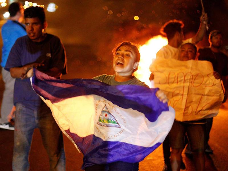 A demonstrator holds up a Nicaragua flag next to a burning barricade as demonstrators take part in a protest over a controversial reform to the pension plans of the Nicaraguan Social Security Institute (INSS) in Managua, Nicaragua (REUTERS/Jorge Cabrera)