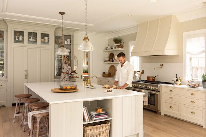 In the kitchen, David Jones cuts bread on the Caesarstone Calacatta Nuvo countertop, while Kim Vaage Jones reaches into a cabinet designed by Sage Cabinetry.