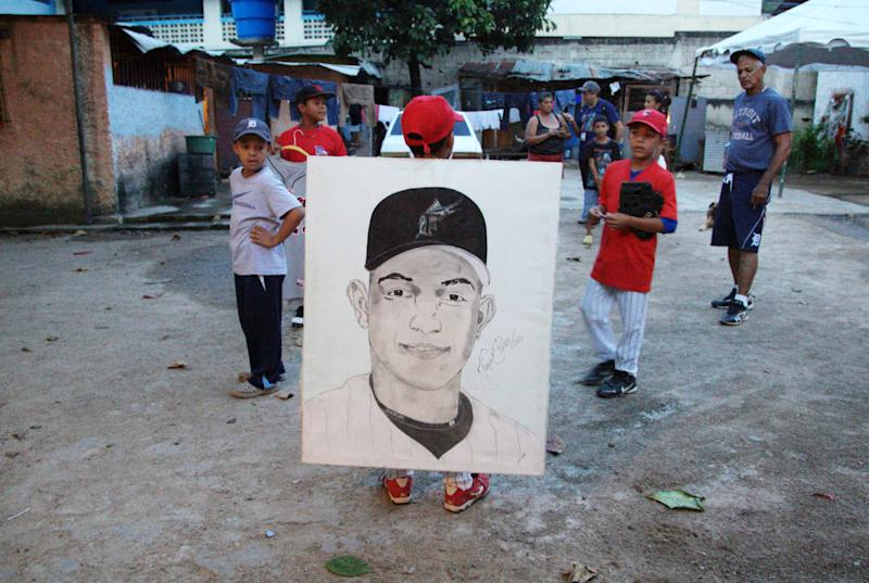 In this Oct. 25, 2012 photo, young baseball players who are cousins of Detroit Tigers' Miguel Cabrera hold a painting of him in Maracay, Venezuela. Many of the boys say they hope to one day follow in the steps of Cabrera, who learned the sport on the very same field they play on and is now in the World Series. (AP Photo/Ariana Cubillos)
