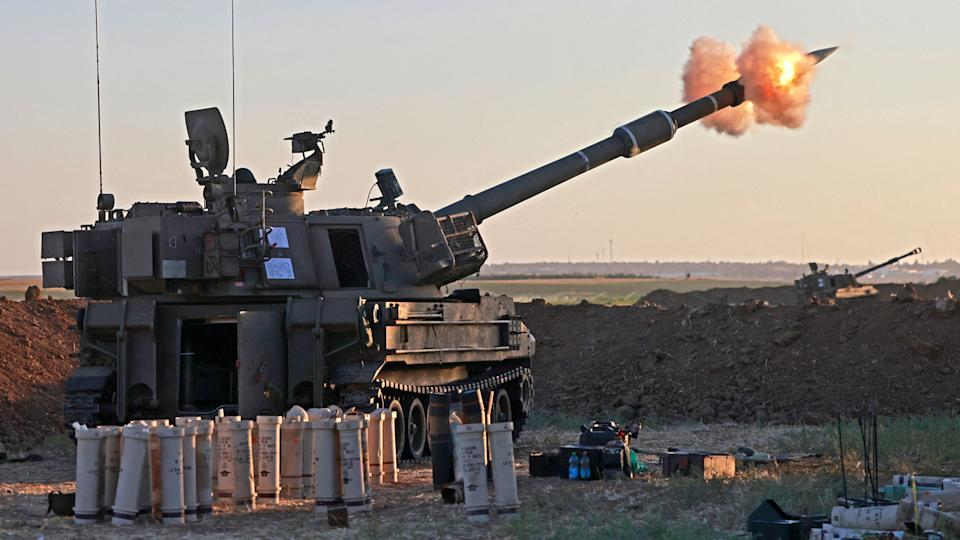 Israeli soldiers fire a 155mm self-propelled howitzer towards the Gaza Strip from their position along the border, on May 18, 2021. (Menahem Kahana/AFP via Getty Images)