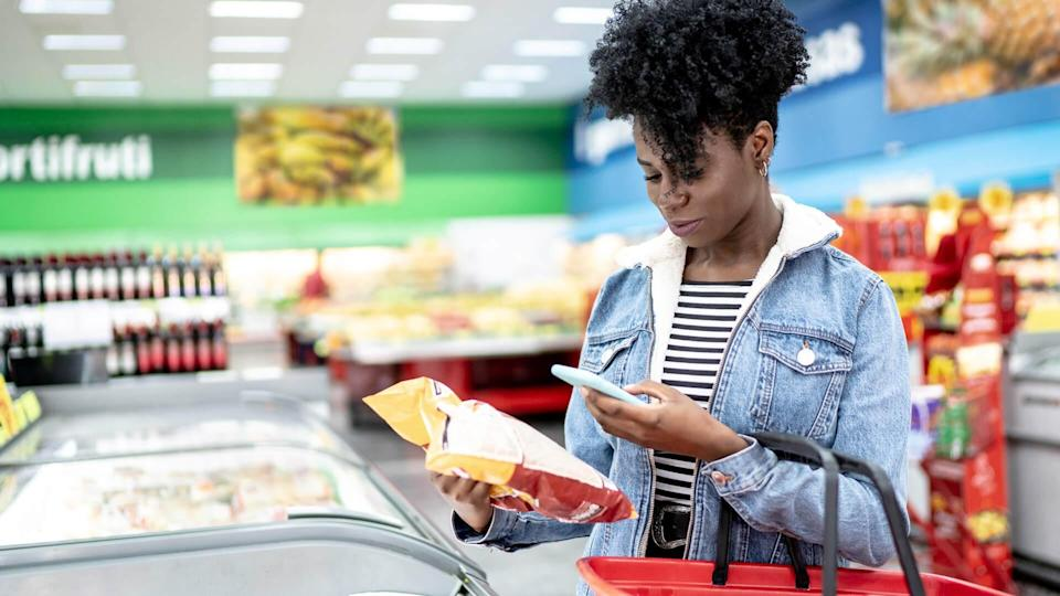 Woman is shopping in supermarket and scanning barcode with smartphone.