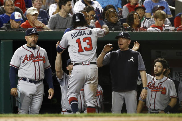 Atlanta Braves' Ronald Acua Jr. (13) high-fives teammates and coaches in the dugout after scoring on Nick Markakis' sacrifice fly during the fifth inning of the team's baseball game against the Washington Nationals, Friday, Sept. 13, 2019, in Washington. (AP Photo/Patrick Semansky)