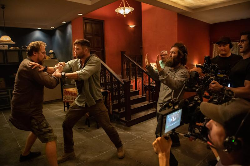 """Director Sam Hargrave (right) goes over a scene with David Harbour and Chris Hemsworth on the set of """"Extraction."""""""