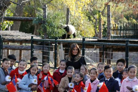 First lady Melania Trump poses for photos with children in front of a panda section as she visits Beijing Zoo in Beijing, China, Nov. 10, 2017. (Reuters/Thomas Peter)