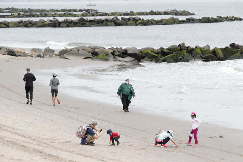 Children play in the sand while others jog as a New York City Parks officer, center, walks the beach making sure no one goes in the water, at Coney Island Beach during the current coronavirus outbreak, Sunday, May 24, 2020, in New York. Swimming is prohibited at New York City beaches. (AP Photo/Kathy Willens)