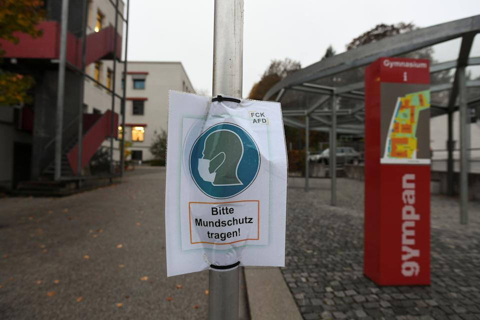 "A sign reading ""Please wear a face mask"" is seen in front of the local high school prior to an ordered lock-down due to the further spreading of the coronavirus disease (COVID-19) in Pfarrkirchen, Germany, October 26, 2020. REUTERS/Andreas Gebert"