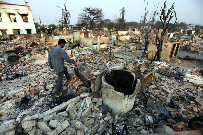 A man walks among debris of buildings destroyed during ethnic unrest between Buddhists and Muslim in Meikhtila, about 550 kilometers (340 miles) north of Yangon, Myanmar, Monday, March 25, 2013. Sectarian clashes between Buddhists and Muslims in Meikhtila spread to at least two other towns in the country's heartland over the weekend, undermining government efforts to quash an eruption of violence that has killed dozens of people and displaced 10,000 more. On Sunday, Vijay Nambiar, the U.N. secretary-general's special adviser on Myanmar, toured Meikhtila, where soldiers were able to impose order after several days of anarchy, and called on the government to punish those responsible. (AP Photo/Khin Maung Win)