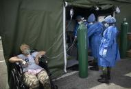 A woman who suffers from COVID-19 receives oxygen at a field hospital set up in the parking lot of the Poliedro de Caracas auditorium, in Venezuela, Sunday, March 21, 2021. (AP Photo/Ariana Cubillos)