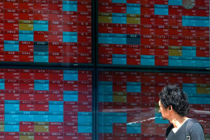 In this Aug. 9, 2019, photo, a man looks at an electronic stock board showing Japan's Nikkei 225 index at a securities firm in Tokyo. Asian shares were mostly higher Wednesday, Aug. 14, 2019 after the U.S. said it would hold off on tariffs of Chinese imports of mobile phones, toys and several other items typically on holiday shopping lists. (AP Photo/Eugene Hoshiko)