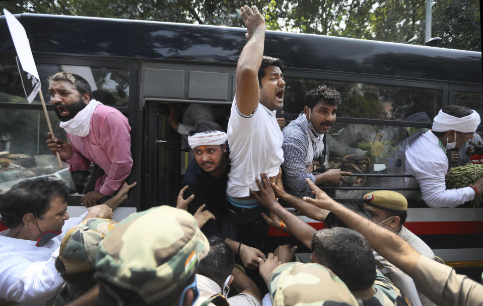 Member of India's opposition Congress party shout slogans as they are detained during a protest against agriculture bills in New Delhi, India, Monday, Sept. 21, 2020. Amid an uproar in Parliament, Indian lawmakers on Sunday approved a pair of controversial agriculture bills that the government says will boost growth in the farming sector through private investments. (AP Photo/Manish Swarup)