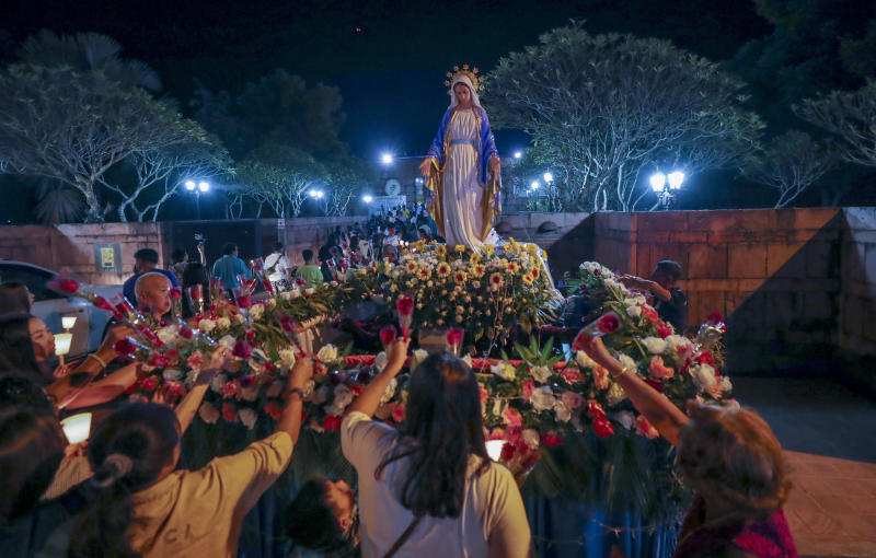 In this Friday, Oct. 18, 2019, photo, Catholic worshippers lay flowers at the base of a Mother Mary statue at the Christ Church in Songkhon village, Mukdahan province, northeastern of Thailand. There are about 388,000 Catholics in Thailand, representing 0.58 percent of the country's 69 million population. (AP Photo/Sakchai Lalit)