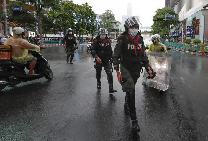 Thai police with riot shields take position in a business district where anti-government protesters sayid they will meet in Bangkok, Thailand, Friday, Oct. 16, 2020. Police announced Friday they would block roads leading to Bangkok's Rajprasong intersection, where Thursday's rally was held, after protesters called on supporters to mass again. (AP Photo/Sakchai Lalit)
