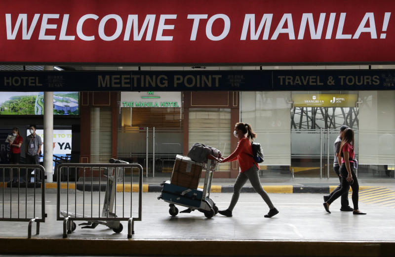 FILE PHOTO: A woman wearing a protective face mask arrives at the Manila's international airport, Philippines on Monday Feb. 3, 2020. (AP Photo/Aaron Favila)
