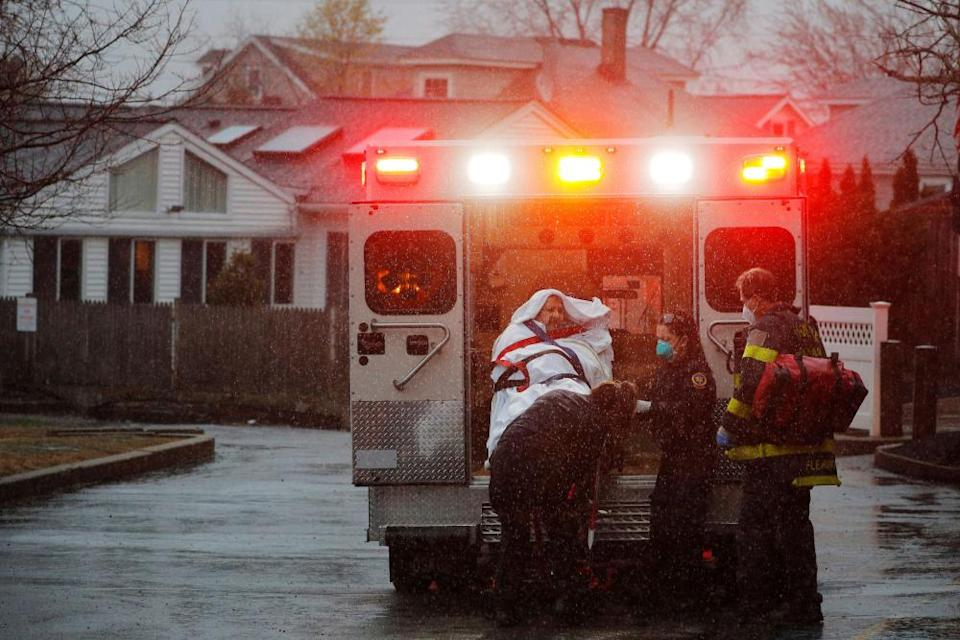 Medics load a patient into the ambulance at the West Revere Health Center in Revere, Massachusetts.