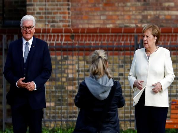 German President Frank-Walter Steinmeier and Chancellor Angela Merkel pose before the start of the festivities to mark the 30th anniversary of the German reunification in Potsdam.