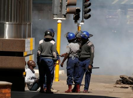 Riot police detain a man during clashes after police banned planned protests over austerity and rising living costs called by the opposition Movement for Democratic Change (MDC) party in Harare