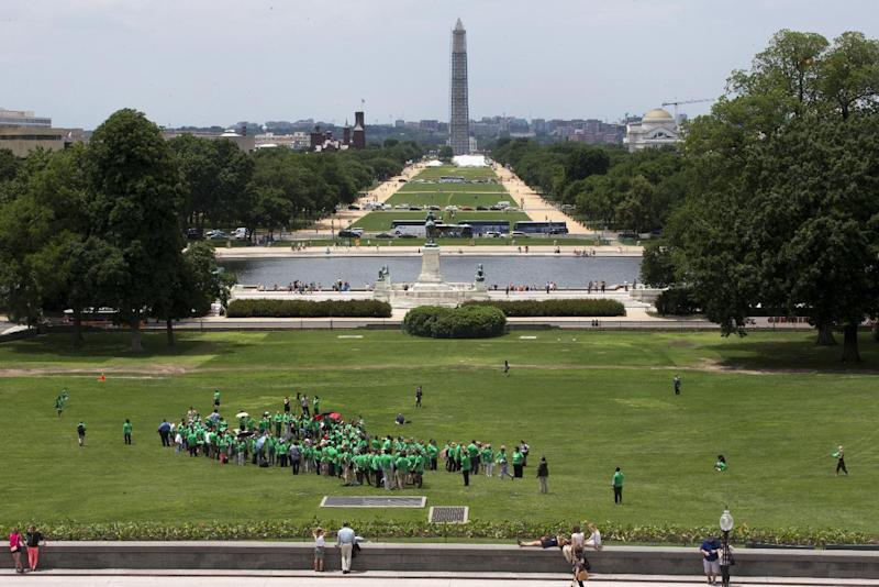 "Supporters and family members of the Newtown, Conn. shooting victims form a human ""ribbon"" on the West Front of the Capitol in Washington, Thursday, June 13, 2013, looking toward the Washington Monument, on the sixth month anniversary of the Newtown shootings. (AP Photo/Jacquelyn Martin)"