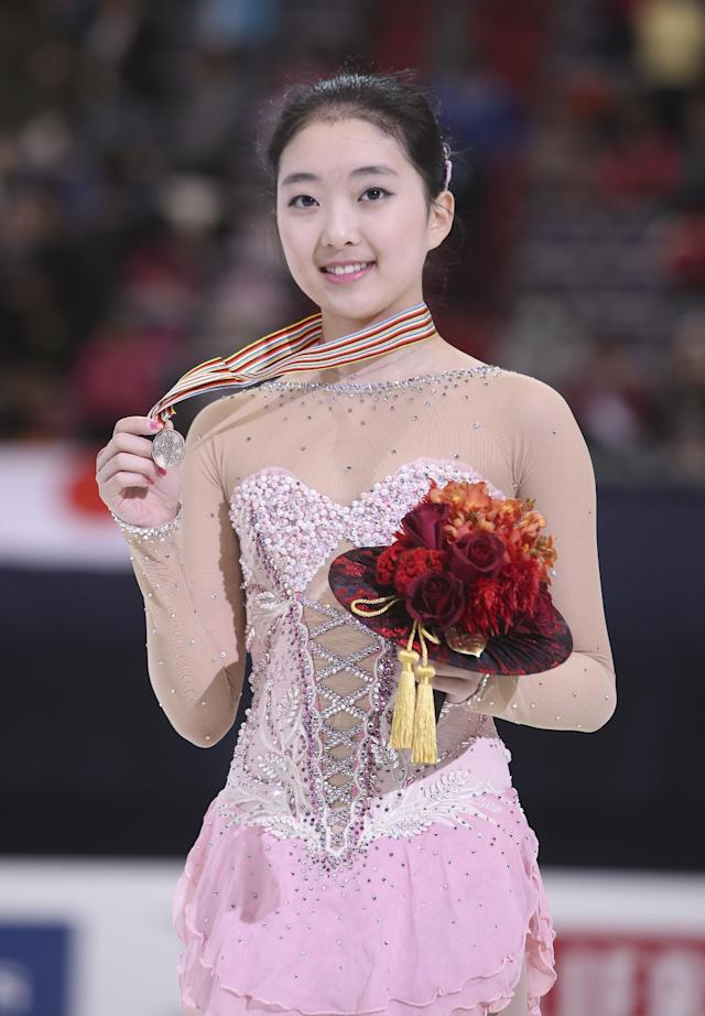 China's Li Zijun poses with the bronze medal for photos at the ladies free skating of the Four Continents Figure Skating Championships in Taipei, Taiwan, Saturday, Jan. 25, 2014. (AP Photo/Chiang Ying-ying)