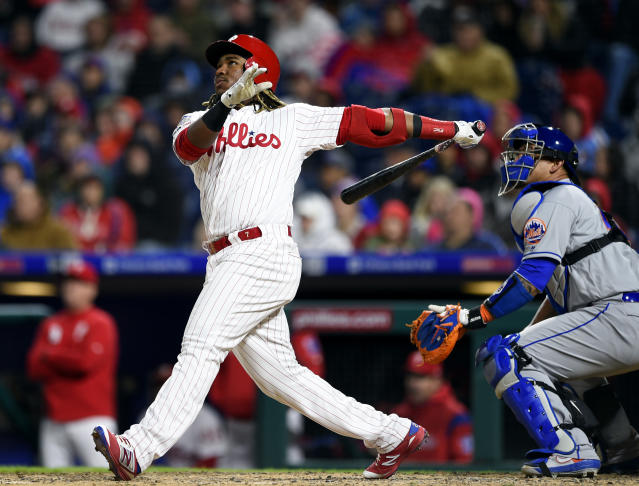Philadelphia Phillies' Maikel Franco, left, watches the ball in front of New York Mets' Wilson Ramos after hitting a two-run home run off Noah Syndergaard during the fourth inning of a baseball game, Monday, April 15, 2019, in Philadelphia. (AP Photo/Derik Hamilton)