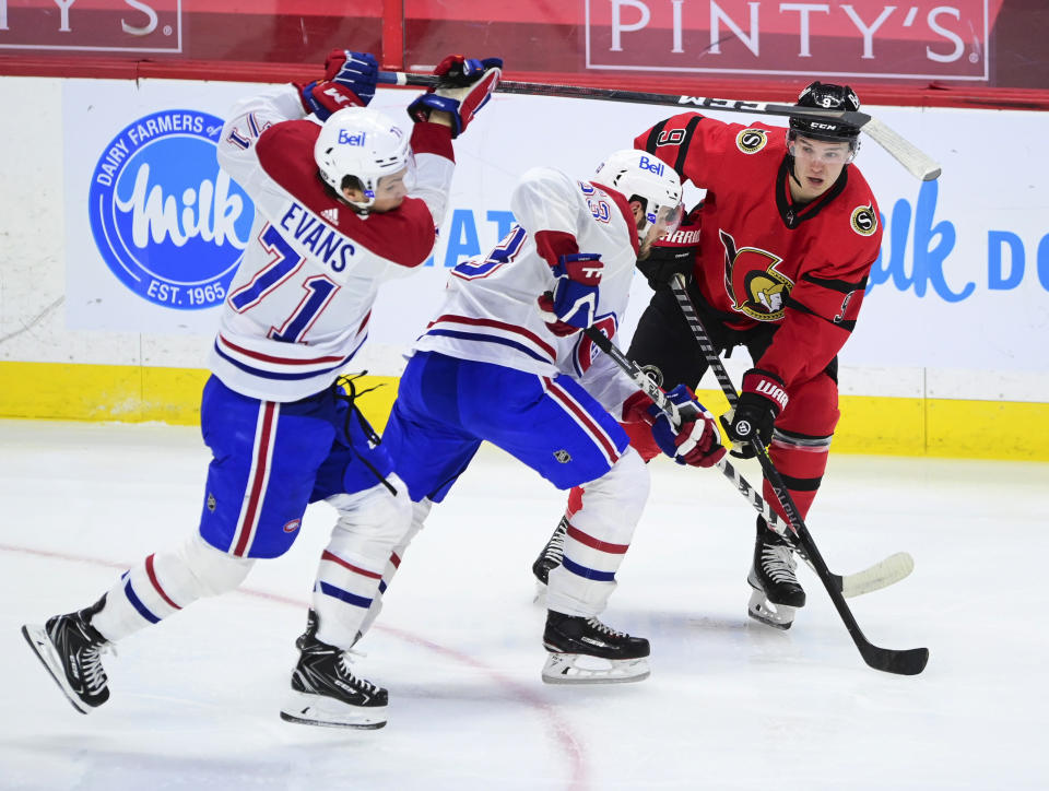 Ottawa Senators' Josh Norris (9) looks for a pass as Montreal Canadiens' Jake Evans (71) and Victor Mete (53) defend during the second period of an NHL hockey game Thursday, April 1, 2021, in Ottawa, Ontario. (Sean Kilpatrick/The Canadian Press via AP)