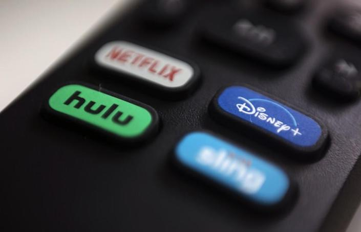 FILE - In this Aug. 13, 2020 file photo, the logos for Netflix, Hulu, Disney Plus and Sling TV are pictured on a remote control in Portland, Ore. As streaming services proliferate, it can be a challenge to keep track of where some favorite TV shows and blockbuster movies are available. (AP Photo/Jenny Kane)