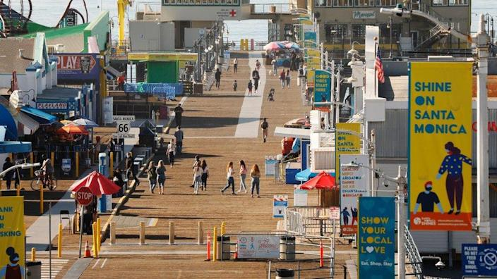Pedestrians enjoy the weather on the Santa Monica Pier which has been temporarily closed January weekends