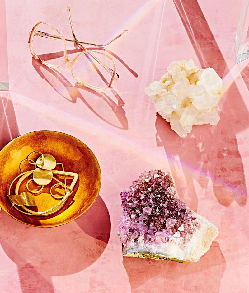 still life of gold dish containing jewelry glasses and healing crystals