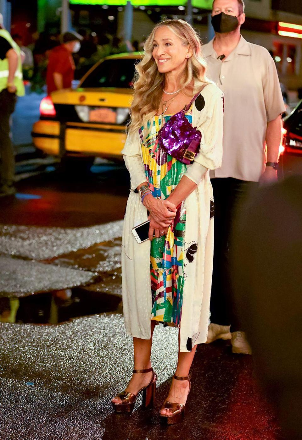"""<p>The cast were seen filming a glamorous night out in New York City, with Carrie dressed in a multi-coloured dress with a delicate coat and metallic gold Saint Laurent platform heels.</p><p><a class=""""link rapid-noclick-resp"""" href=""""https://go.redirectingat.com?id=127X1599956&url=https%3A%2F%2Fwww.net-a-porter.com%2Fen-gb%2Fshop%2Fshoes%3Fcm_sp%3Dtopnav-_-shoes-_-topbar%26facet%3Dbrand_1442&sref=https%3A%2F%2Fwww.harpersbazaar.com%2Fuk%2Ffashion%2Fwhat-to-wear%2Fg37057394%2Fand-just-like-that-style-fashion%2F"""" rel=""""nofollow noopener"""" target=""""_blank"""" data-ylk=""""slk:SHOP MORE SAINT LAURENT SHOES"""">SHOP MORE SAINT LAURENT SHOES</a></p>"""