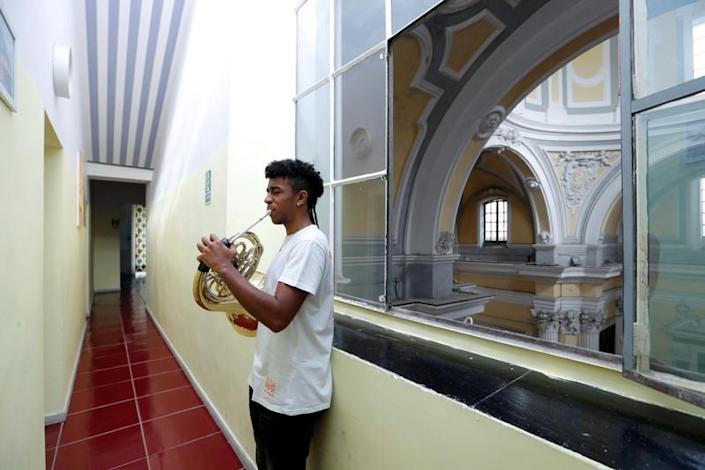 Nico Rodrigues, 21, practises on his French horn in Saint Severo Out of Walls church, close to the Santa Maria della Sanita Basilica in the Rione Sanita neighbourhood in Naples