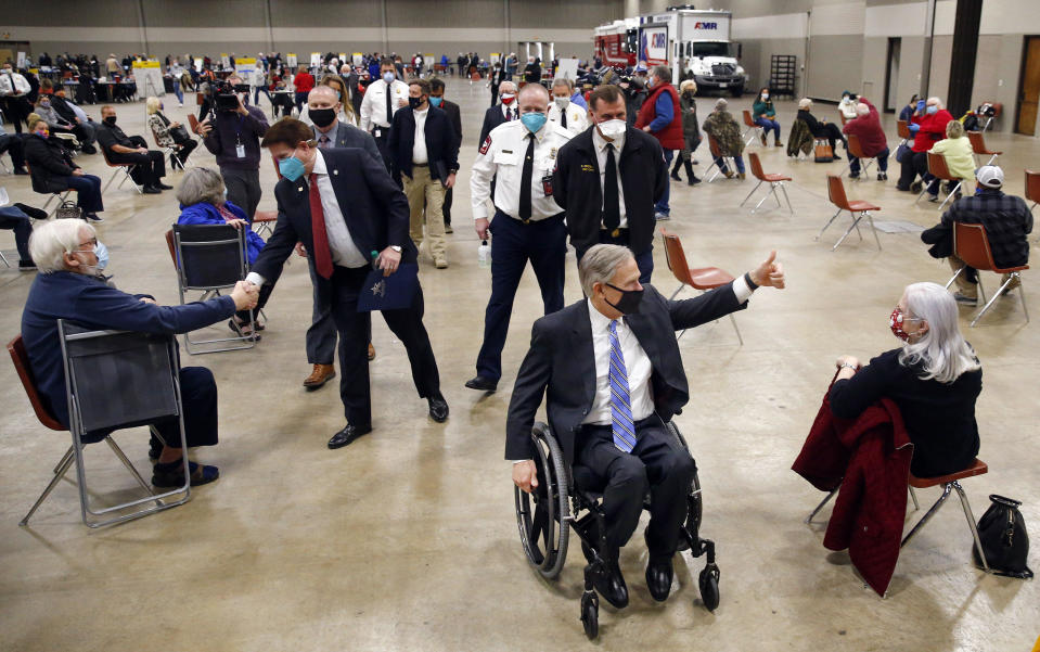 Texas Governor Greg Abbott gives a thumbs up to people who received a COVID-19 shot as he tours a mass vaccination site inside Esports Stadium Arlington & Expo Center in Arlington, Texas, Monday, January 11, 2021. / Credit: Tom Fox / AP