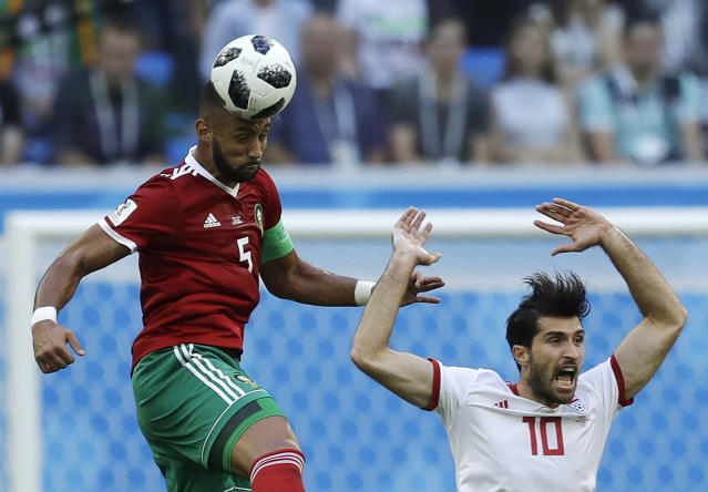 Morocco's Mehdi Benatia, left, and Iran's Karim Ansarifard, right, compete for the ball during the group B match between Morocco and Iran at the 2018 soccer World Cup in the St. Petersburg Stadium in St. Petersburg, Russia, Friday, June 15, 2018. (AP Photo/Themba Hadebe)