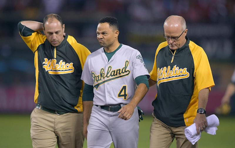 Oakland Athletics center fielder Coco Crisp is assisted off the field after he fell on his back while trying to catch a two-run home run by Los Angeles Angels' Chris Iannetta during the fifth inning of a baseball game, Friday, Aug. 29, 2014, in Anaheim, Calif. (AP Photo/Mark J. Terrill)
