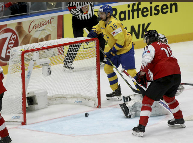 Sweden's Marcus Kruger, center, scores as Austria's Patrick Peter, right, looks on during the Ice Hockey World Championships group B match between Sweden and Austria at the Ondrej Nepela Arena in Bratislava, Slovakia, Thursday, May 16, 2019. (AP Photo/Ronald Zak)