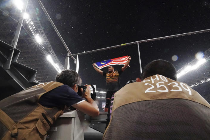 Photographers take pictures as Muhammad Ziyad Zolkefli of Malaysia reacts after competing in the men's shot put F20 final during the Tokyo 2020 Paralympics Games at the National Stadium in Tokyo, Japan Tuesday, Aug. 31, 2021. Zolkefli appeared to have won gold in the shot put in the F20 class. But after the victory on Tuesday, he was disqualified because he had shown up late for the competition. (AP Photo/Eugene Hoshiko)