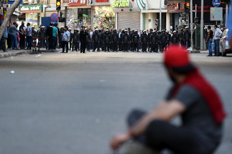 A protester sits in front of riot policemen during a demonstration on April 15, 2016 in central Cairo against a controversial deal to hand two islands in the Red Sea to Saudi Arabia