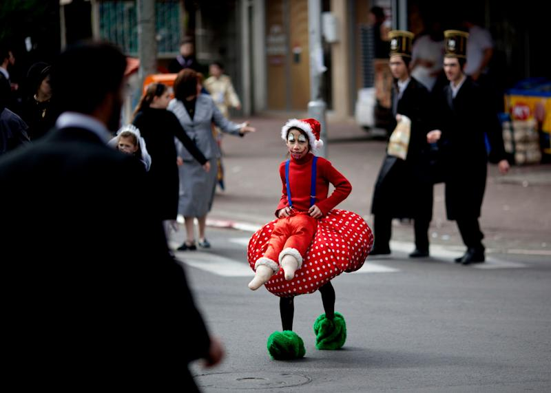 An Ultra Orthodox Jewish girl dressed wearing a costume crosses the street during the Purim festival in the ultra-Orthodox town of Bnei Brak, Israel, Sunday, Feb. 24, 2013. (AP Photo/Ariel Schalit)