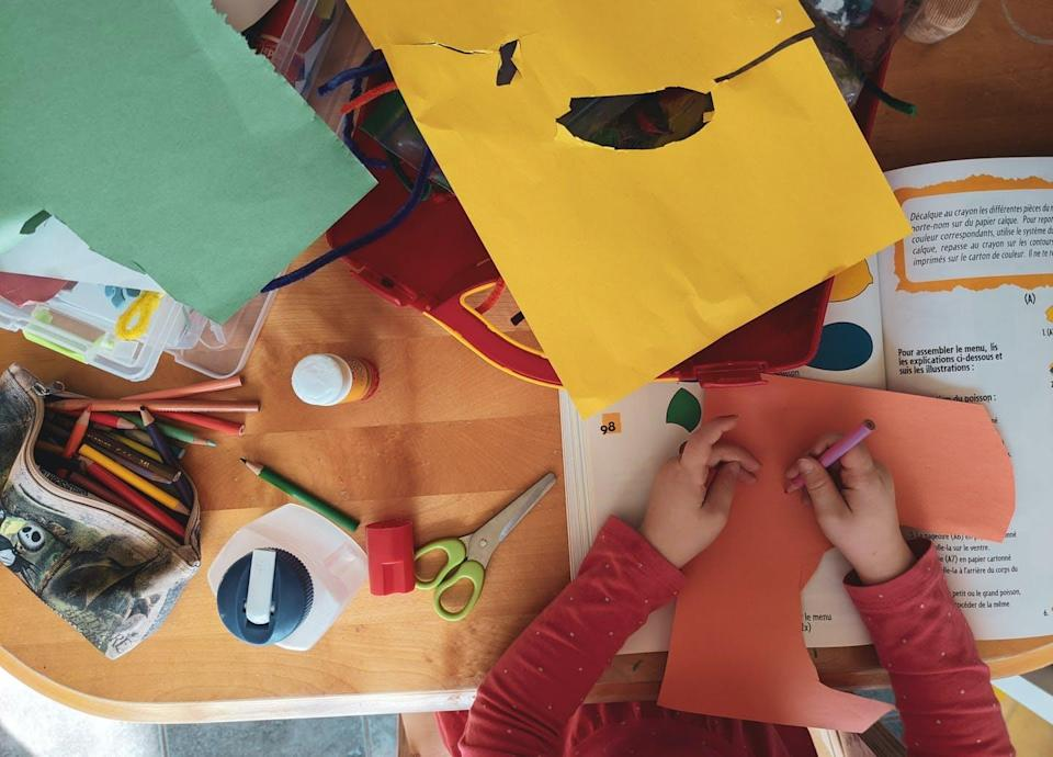 A child holds a pencil crayon to a cut piece of orange construction paper, the photo is from the top-down and the desk is covered with other craft materials