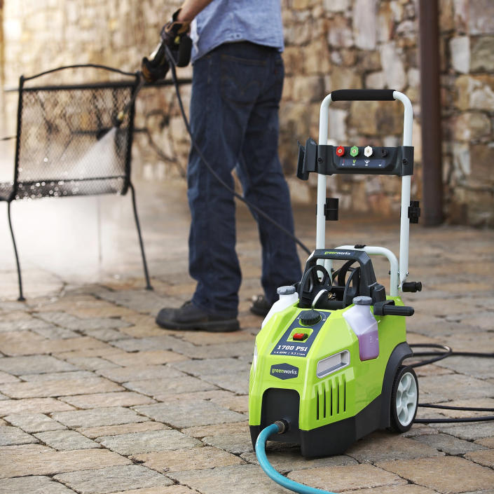 """This July 9, 2013 publicity photo provided by Lowe's Home Improvement shows a Greenworks 1700 PSI ,1.4 GPM Electric Pressure Washer being used to clean a patio chair. Lowe's Home Improvement spokeswoman Colleen Maiura said, """"Monthly cleaning and maintenance can help the furniture maintain a good appearance and make your investment last longer."""" (AP Photo/Lowe's Home Improvement)"""