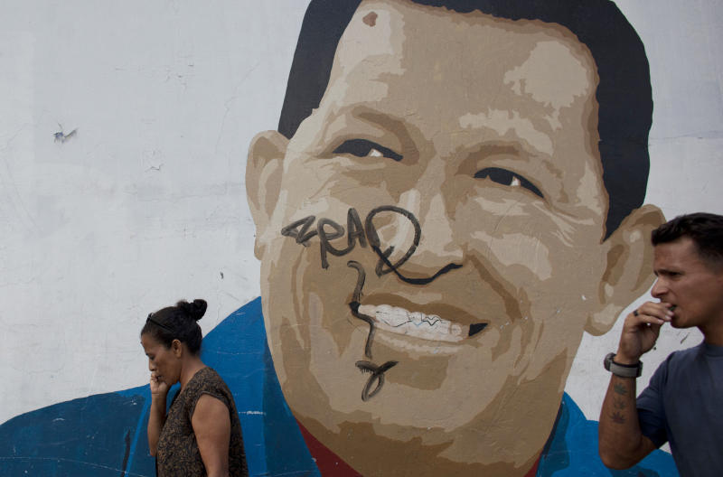 Pedestrians walk past a mural of Venezuela's President Hugo Chavez in Caracas, Venezuela, Wednesday, Jan. 9, 2013. Venezuela's congress has voted to postpone the inauguration of President Hugo Chavez, which was scheduled for Thursday, to let him recover from cancer surgery in Cuba. Critics say that violates the country's constitution. On Wednesday, Venezuela's Supreme Court backed the congress ruling Chavez's inauguration can be postponed. (AP Photo/Ariana Cubillos)