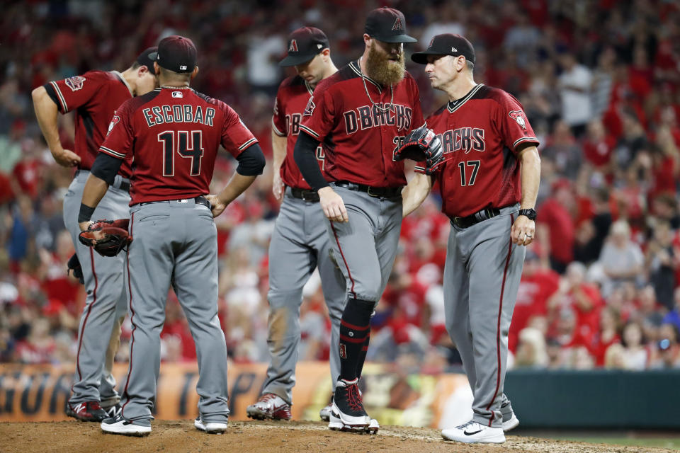 Arizona Diamondbacks relief pitcher Archie Bradley, center, is relieved by manager Torey Lovullo (17) in the eighth inning of a baseball game against the Cincinnati Reds, Saturday, Aug. 11, 2018, in Cincinnati. (AP Photo/John Minchillo)