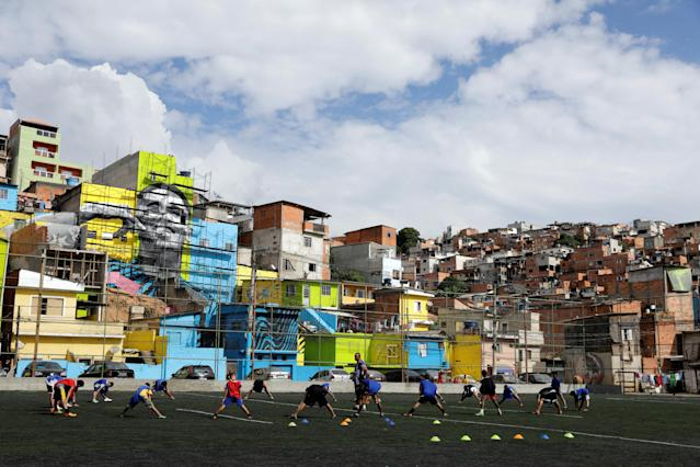 Players attend a training in a field with the image of Brazil' soccer player Gabriel Jesus in the background, painted on the walls of houses in the neighbourhood he lived in during his childhood in Sao Paulo, Brazil May16, 2018. REUTERS/Paulo Whitaker