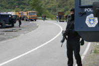 Kosovo police officers patrol a road near the northern Kosovo border crossing of Jarinje, Tuesday, Sept. 21, 2021. Tensions soared Monday when Kosovo special police with armored vehicles were sent to the border to impose a rule on temporarily replacing Serb license plates from cars while they drive in Kosovo. (AP Photo/Visar Kryeziu)