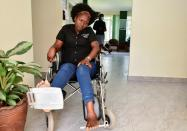 Irene Abalo, a journalist working with The Daily Monitor newspaper, sits on a wheelchair after she was injured following an attack by security officials in Kampala
