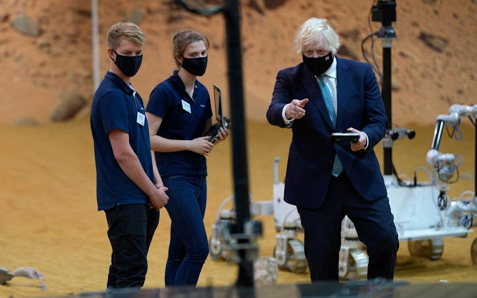 Boris Johnson is shown one of three prototype system testbed Mars Rovers at the Airbus Defence and Space plant in Stevenage - /AP