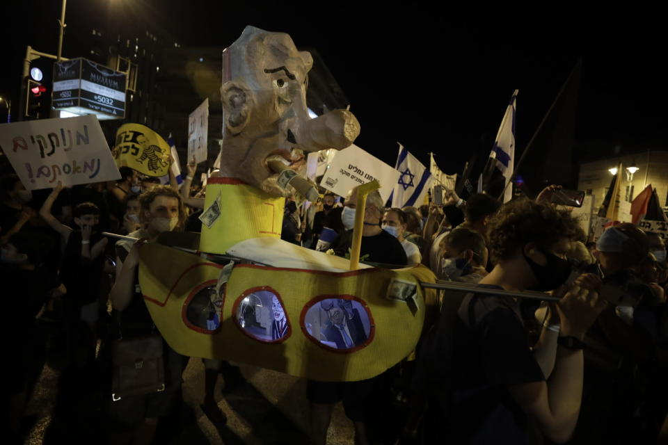 Israelis hold signs and chant slogans during a demonstration against Israeli Prime Minister Benjamin Netanyahu near the Prime Minister's residence in Jerusalem, Saturday, Aug. 15, 2020. (AP Photo/Sebastian Scheiner)