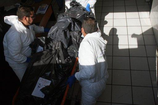 Forensic technicians carry on a trolley into the morgue part of the 15 corpses found earlier