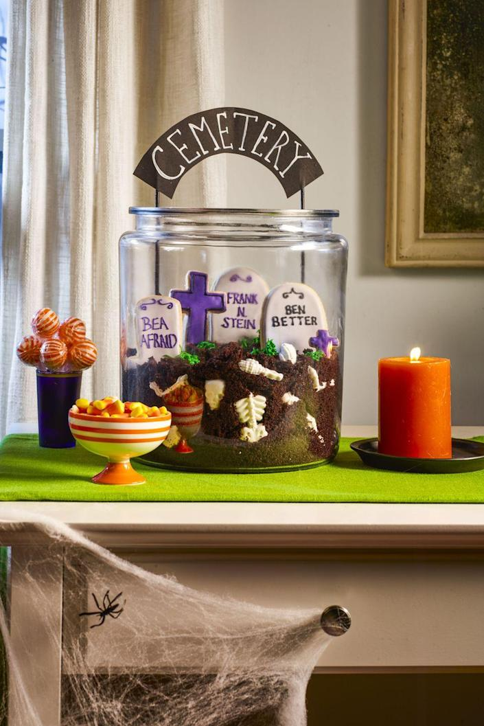 """<p>This is one dessert they'll be dying to dig into! Fill a large glass cookie jar with crumbs from your favorite chocolate cake along with white chocolate bones (we used <span class=""""redactor-unlink"""">skeleton candy molds from Wilton</span>). Layer in tombstone sugar cookies (we used <span class=""""redactor-unlink"""">tombstone and cross cutters</span>) decorated with gray, black, and purple royal icing. Pipe in tufts of grass using green-tinted buttercream. Push in a cemetery sign made from cardstock and painted wood skewers.</p>"""