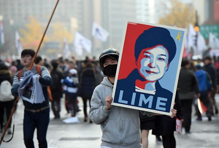 A protester holds a placard with a portrait of South Korea's President Park Geun-Hye, during an anti-government rally in Seoul (AFP Photo/Jung Yeon-Je)